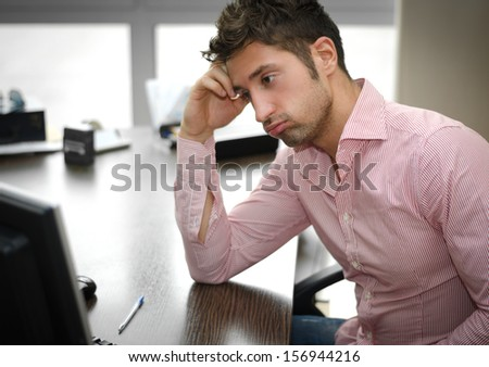 Tired or frustrated young man working in office looking at computer screen - stock photo
