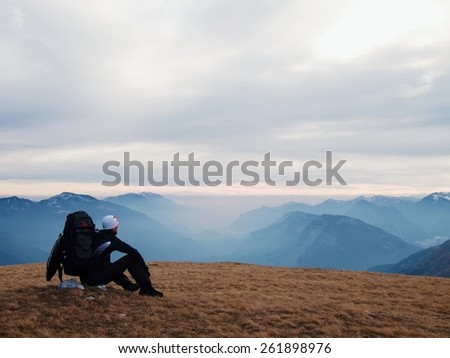 Tired out tourist in black with backpack is sitting on stone in meadow and watching into misty valley. Autumn misty day in mountains.  - stock photo