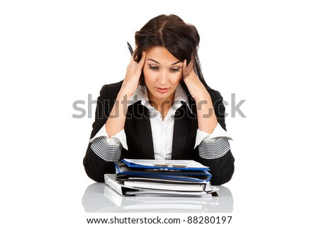 tired overworked business woman sitting at the desk with folder stack holding head with hands. Isolated on white background. - stock photo
