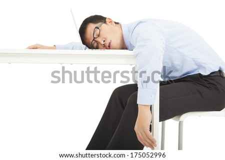 Tired overworked businessman sleeps on desk - stock photo