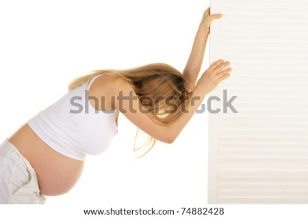 tired pregnant woman leaned on the door isolated on white - stock photo