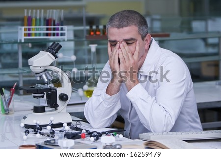 Tired researcher at his workplace. - stock photo