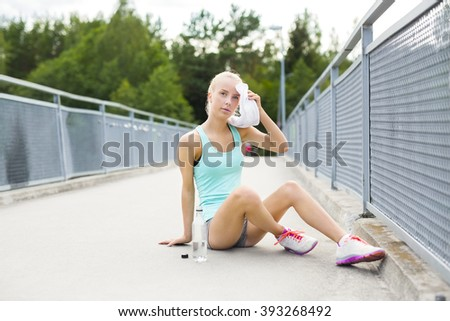 Tired runner sitting on the ground and having a break - stock photo