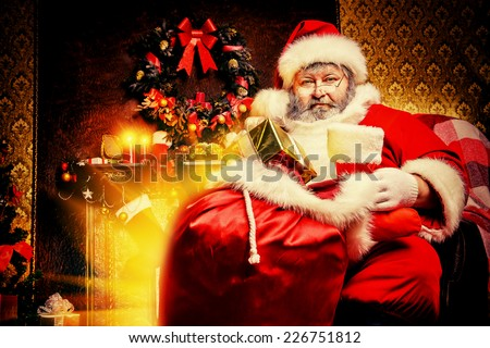 Tired Santa Claus stands by the fireplace with a bag of gifts. Christmas home decoration. - stock photo
