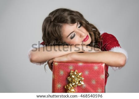 Tired Santa helper girl sleeping comfortable on big red box with golden ribbon over gray studio background.