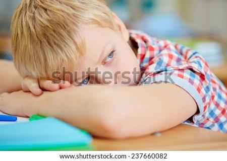 Tired schoolboy having rest - stock photo