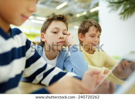 Tired schoolboy looking at digital tablet display with indifferent expression - stock photo