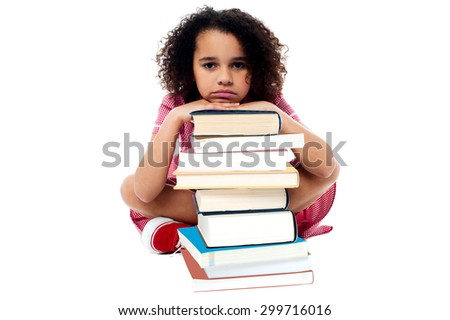 Tired schoolgirl resting her arms on books - stock photo