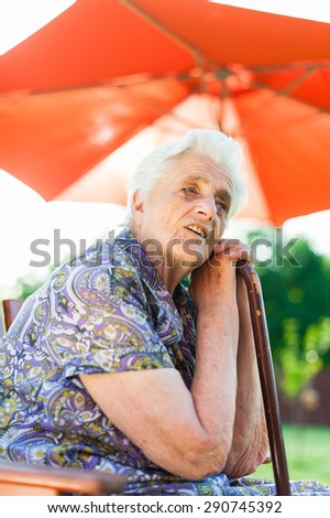 Tired senior woman leaning on her stick - stock photo