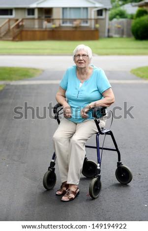 Tired senior woman sitting on walker - stock photo