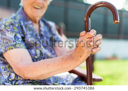 Tired senior woman with her cane - stock photo
