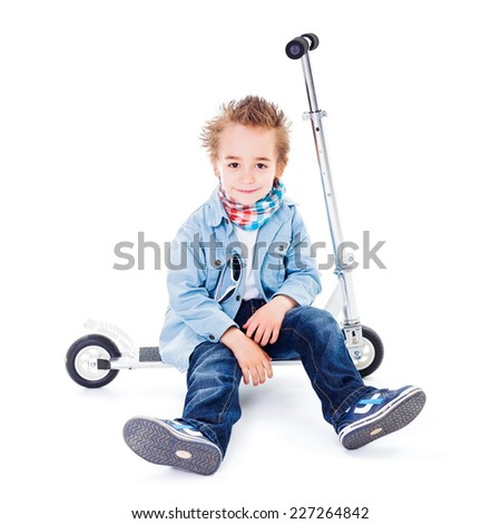 Tired small boy in jeans, resting on scooter - stock photo
