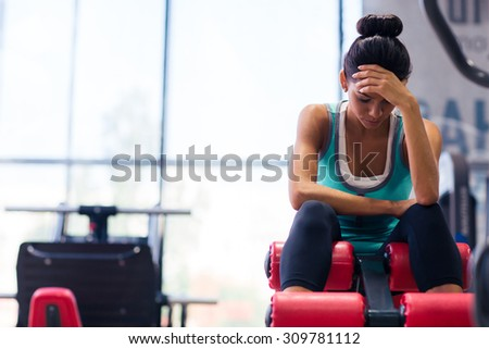 Tired sports woman sitting on exercises machine in fitness gym - stock photo