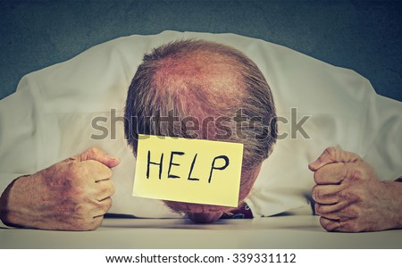 Tired, stressed senior employee needs help. Frustrated elderly man with note on his forehead leaning his head on the table exhausted. Long working hours, aging concept - stock photo