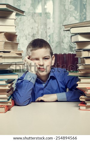 Tired student at a desk between stacks of books