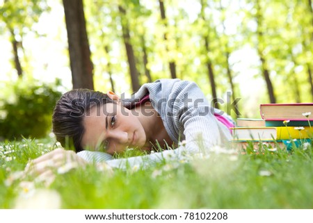 tired student girl lying on grass next to books - stock photo