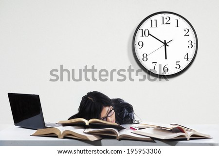 Tired student girl with glasses sleeping on the books - stock photo