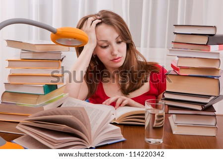 Tired student having a lot to read. Student girl with lot of books around. Student is studding. Study up. - stock photo