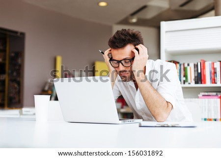 Tired student or businessman working with laptop in the office - stock photo