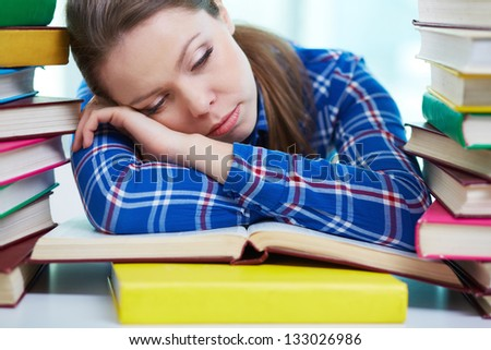 Tired student sleeping over textbooks - stock photo