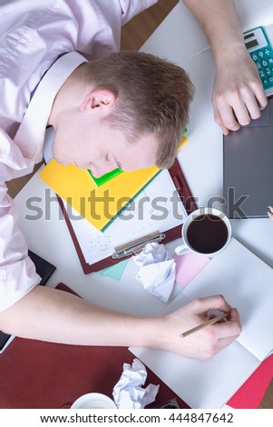 Tired student sleeping with the head on a desk full of notes with pencil in his hand