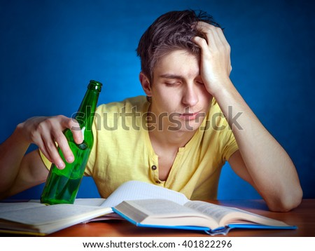 Tired Student with the Beer on the Blue Background - stock photo