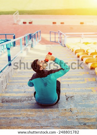 tired sweaty sportsman drinking water at the stadium on the stairs - stock photo