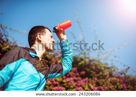 tired sweaty sportsman pouring water in the park - stock photo