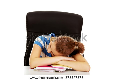 Tired teenage woman sleeping on desk - stock photo