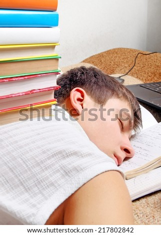 Tired Teenager sleeping on the Sofa with the Books - stock photo