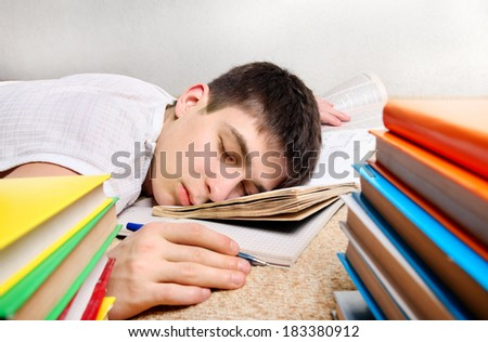 Tired Teenager sleeps after Learning on the Sofa with the Books - stock photo