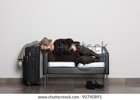 Tired tourist in anticipation of landing on aircraft (ferry, train or bus). Flight delay due to weather conditions. Waiting hall. - stock photo