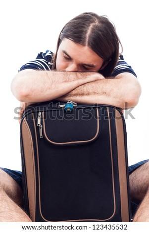 Tired traveler tourist man sleeping on luggage, isolated on white background. - stock photo