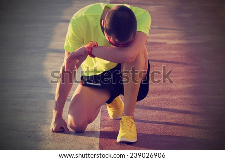 Tired urban jogger making a pause after forcing his body. - stock photo