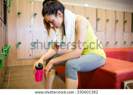 Tired woman after a workout in the gym locker room - stock photo