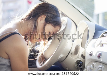 Tired woman asleep on steering wheel in her car - stock photo