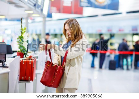 Tired woman at international airport in terminal at check-in desk. Upset business passenger waiting. Canceled flight due to pilot strike. Heathrow, London. - stock photo