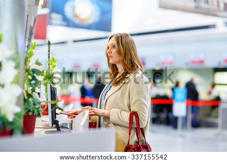 Tired woman at international airport in terminal at check-in desk. Upset sad business passenger waiting. Canceled flight due to pilot strike. - stock photo