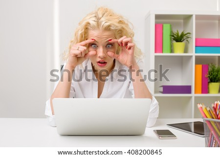 Tired woman at the office looking at computer and holding her eyes open