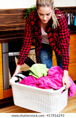 Tired woman carrying laundry basket in kitchen  - stock photo