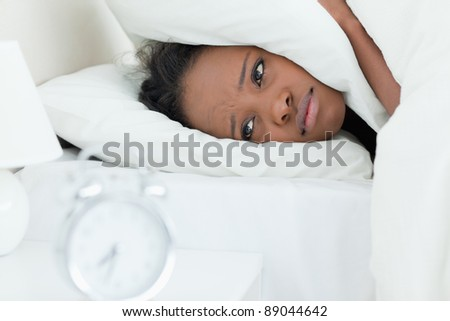 Tired woman covering her ears while her alarm clock is ringing in her bedroom - stock photo