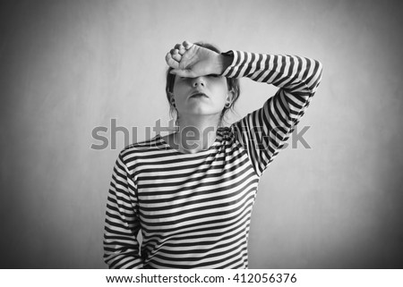 Tired woman in a striped vest