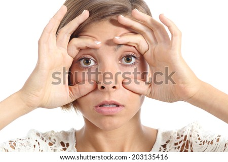 Tired woman opening her eyes with the fingers isolated on a white background - stock photo
