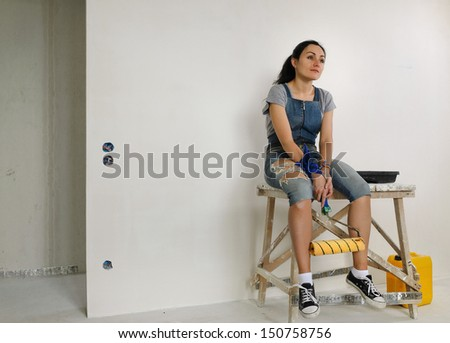 Tired woman relaxing while painting a wall sitting on a wooden trestle with the paint roller dangling between her legs staring into space thinking - stock photo