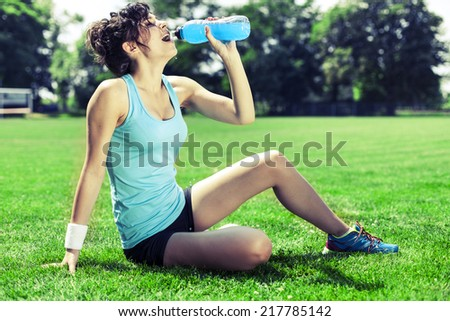 Tired woman runner taking a rest after run, drinking water - stock photo
