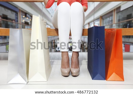 Tired woman sitting near her shopping bags in mall
