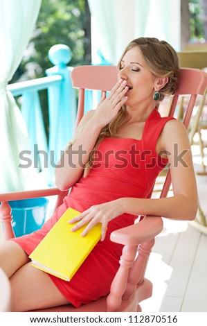 tired woman sitting with book and yawing - stock photo