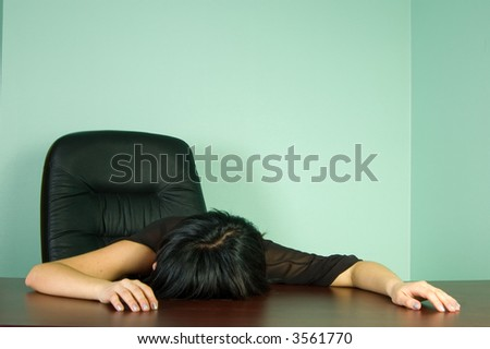 Tired woman sleeping at office desk - stock photo