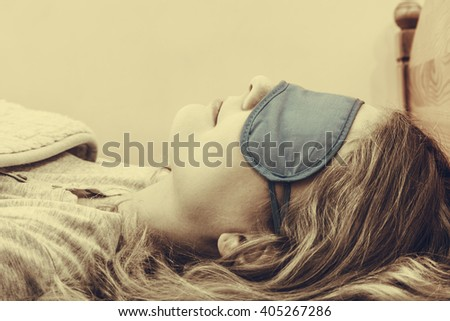 Tired woman sleeping in bed wearing blindfold sleep mask. Young girl taking nap. Sepia. - stock photo