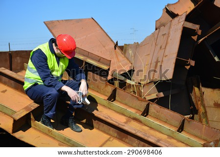 Tired worker on junkyard. Copy space available. - stock photo